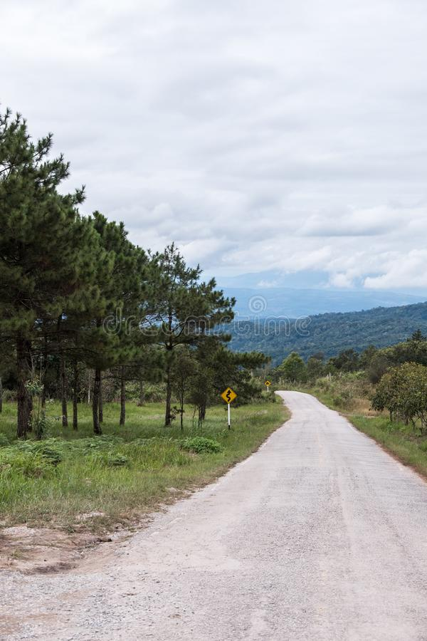 Chemin de terre le long de la colline avec le poteau de signalisation image stock