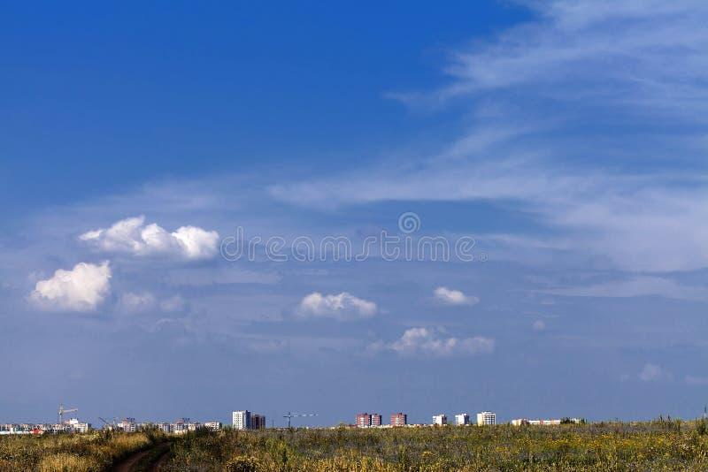Chemin de terre par un champ envahi à la ville sur l'horizon contre un ciel bleu avec les nuages blancs photographie stock libre de droits