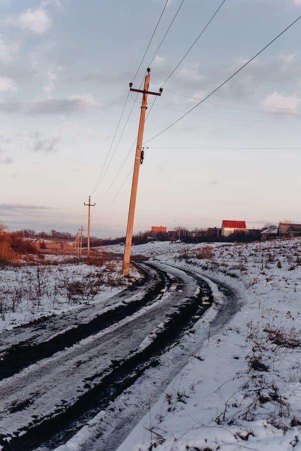 Chemin de terre de pays avec les magmas boueux et neige de fonte en premier ressort au coucher du soleil images stock