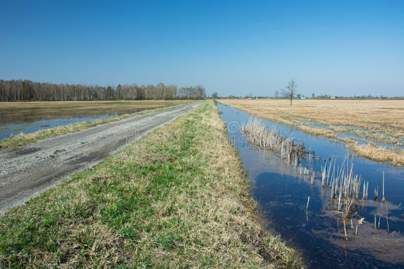 Chemin de terre séparé par une bande d'herbe d'une voie d'eau, d'un horizon et d'un ciel photo stock
