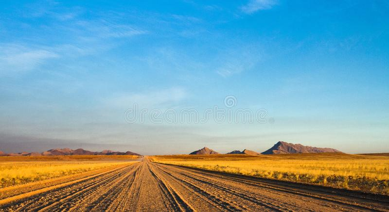 Chemin de terre vide à travers le le désert namibien photo stock