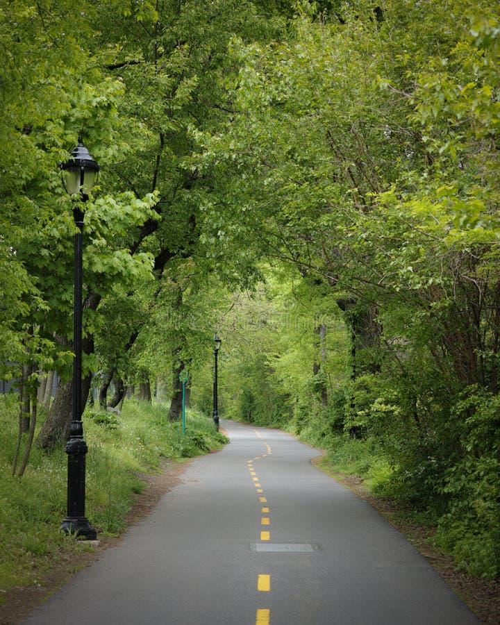 Chemin de vélo de greenway de NYC à travers le fort Washington Park sur un Au foncé photographie stock