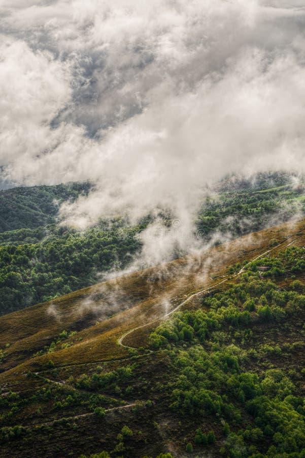 Chemin de zigzag vers le haut de la montagne par le brouillard photo libre de droits