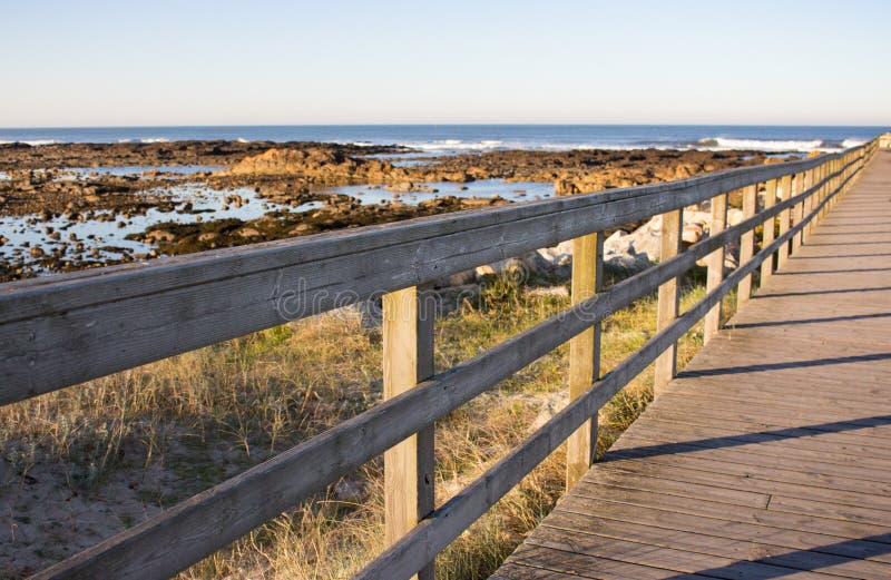Chemin en bois avec la barri?re ? la plage Passage couvert sur le bord de la mer pendant le matin C?te de l'Oc?an Atlantique au P photos libres de droits