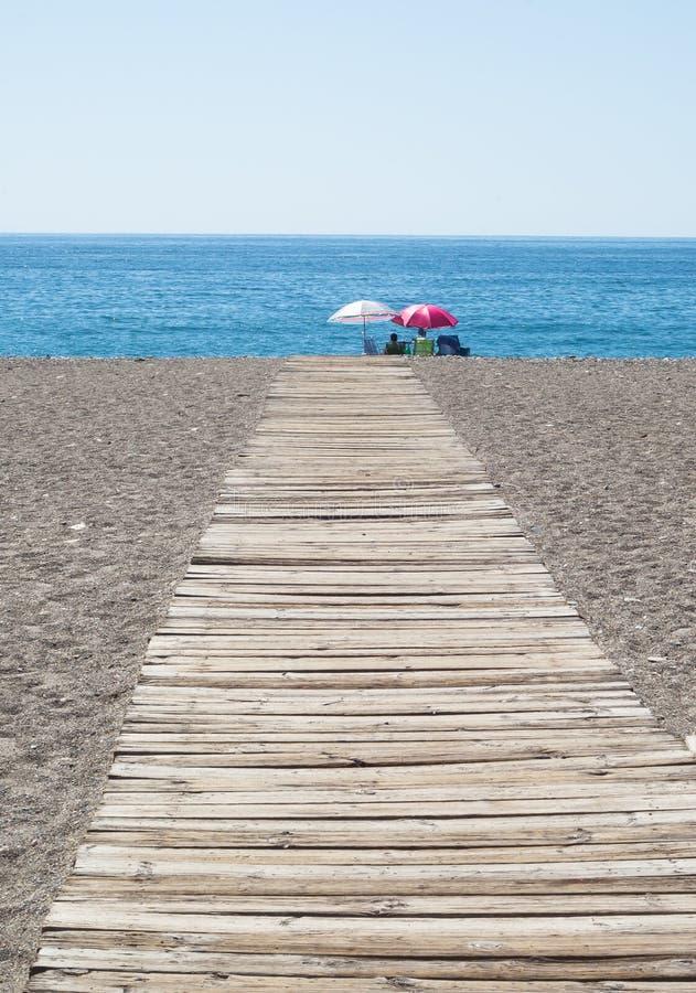 Chemin en bois menant aux gens s'asseyant sur la plage sous des parapluies photographie stock