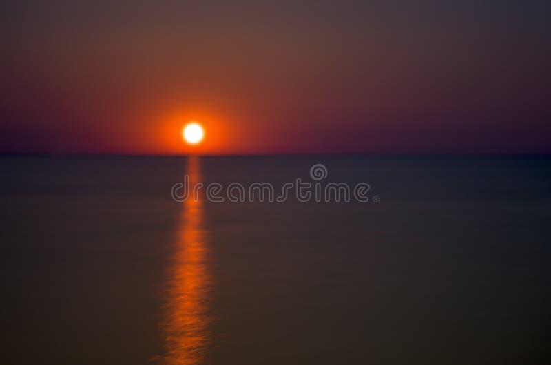 Chemin lunaire de couleur rouge sur la mer images stock