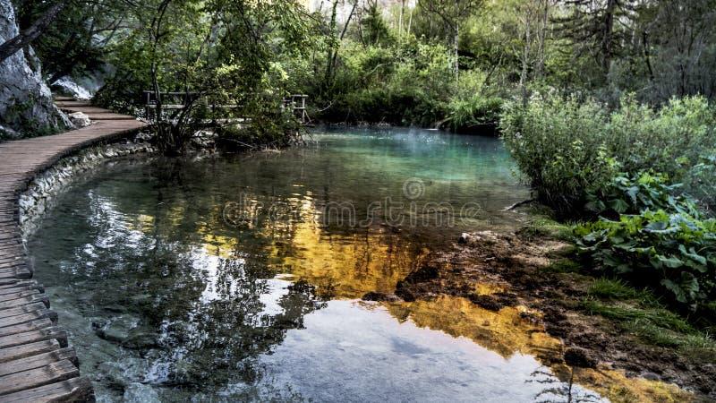 Chemin vide et isolé à côté de l'eau de turquoise dans le parc national de lacs Plitvice en Croatie photo stock