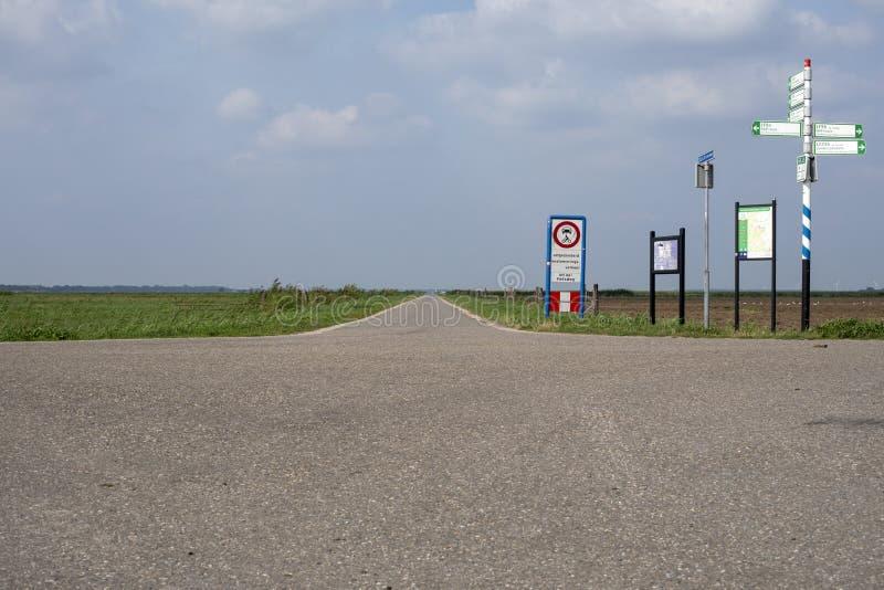 Chemins de cycle, voies pour bicyclettes dans le polder du paysage plat des Pays-Bas à l'horizon un ciel bleu avec les nuages bla photos stock