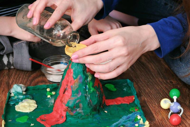 Chemisch experiment De handen van de close-upvrouw ` s goten water van de fles in de trechter van de vulkaan royalty-vrije stock afbeeldingen