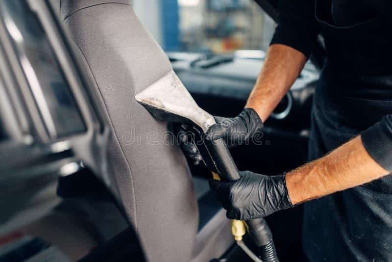 Chemisch reinigen van autozetels met stofzuiger stock fotografie