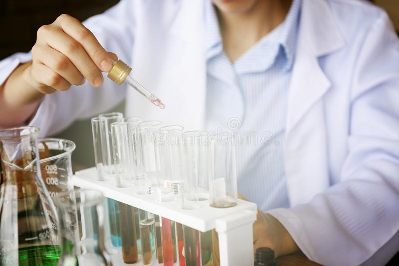 chemische Flüssigkeit des Wissenschaftlerhandtropfens zum Rohr stockfoto