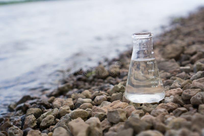 Chemische Flasche mit Wasser, See oder Fluss im Hintergrund stockfotos