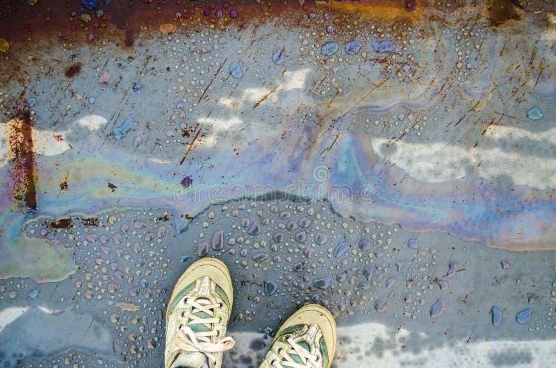 Chemische Flecke des Regenbogens auf dem Wasser in einer Pfütze auf Straße Fahrwerkbeine in den Turnschuhen stockfotografie