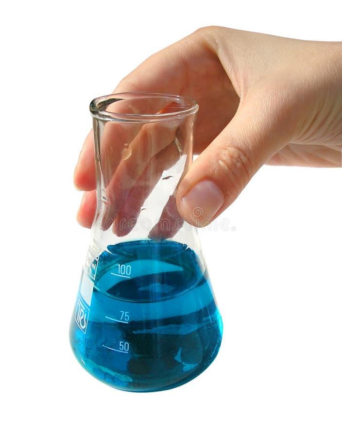 Chemische laboratorium-hand holdingsfles met blauwe vloeistof stock afbeeldingen