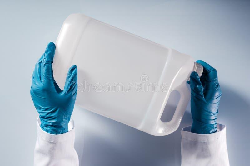 Chemische wetenschapper die witte plastic tankbus openen zonder etiket stock fotografie