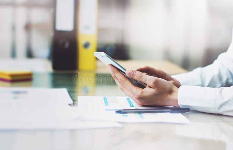 Chemise blanche de port de femme d'affaires de photo, écran émouvant de smartphone Bureau moderne de grenier Fond brouillé horizo photos libres de droits