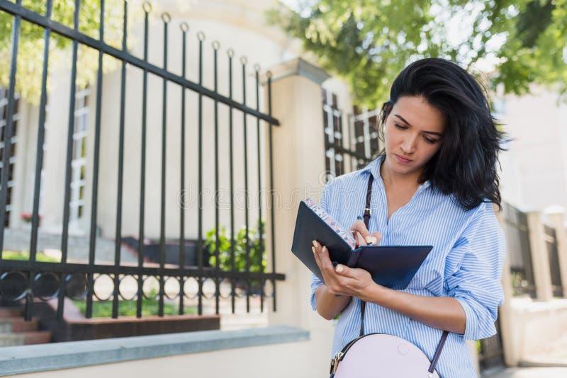 Chemise bleue de port femelle de belle brune heureuse européenne attrayante, faisant des notes dans le carnet tout en marchant de photographie stock libre de droits