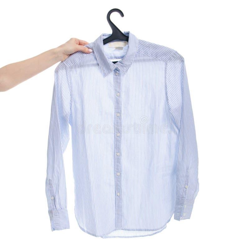 Chemise bleue sur le cintre à disposition photographie stock