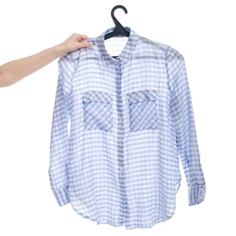 Chemise bleue sur le cintre à disposition image stock