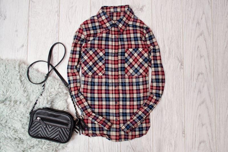 Chemise de dames de plaid, sac à main noir sur la fourrure artificielle Concept à la mode, fond en bois, vue supérieure images stock