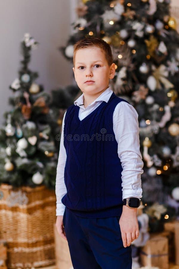Chemise de garçon de huit ans et gilet sur fond d'arbre de Noël photo libre de droits