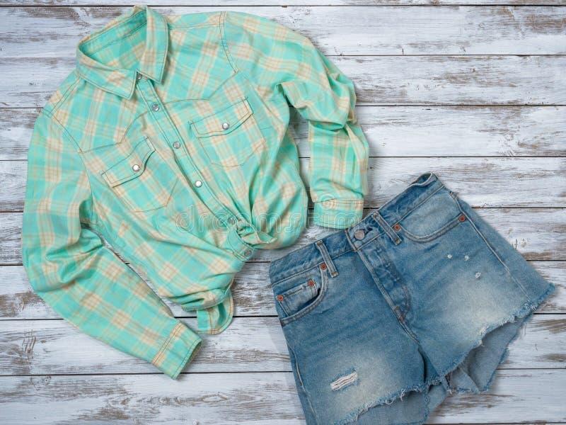 Chemise de plaid de l'habillement des femmes, shorts de denim Équipement de mode, collection d'été de ressort Concept d'achats La photographie stock