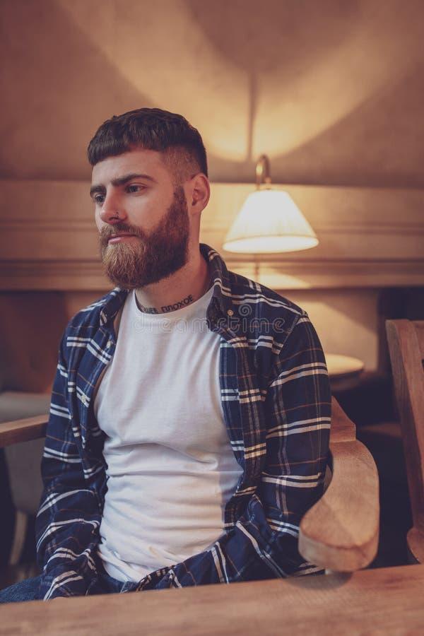 Chemise de plaid de port d'homme barbu bel de portrait au café moderne photographie stock