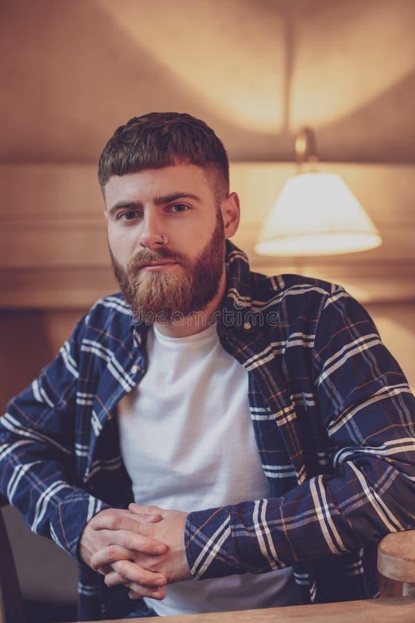 Chemise de plaid de port d'homme barbu bel de portrait au café moderne photos stock