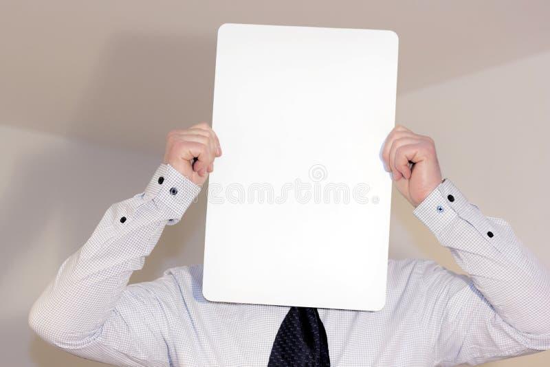 Chemise et lien de port de jeune homme tenant le bord vertical blanc devant son visage image libre de droits