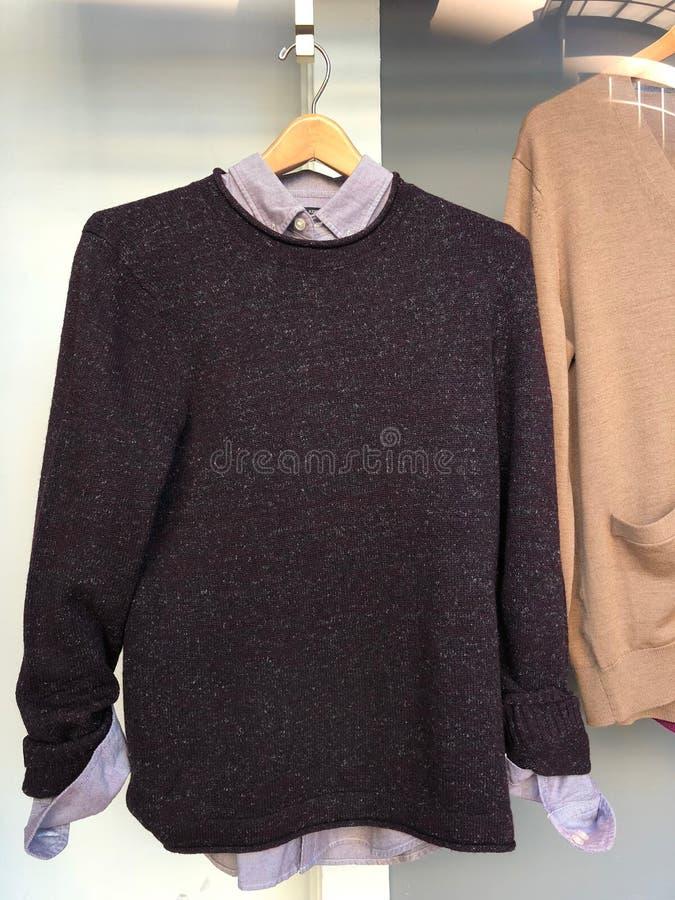 Chemise et pullover de dames accrochant sur le cintre photographie stock