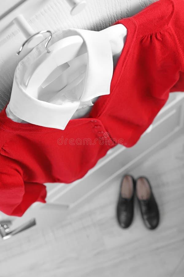 Chemise et pullover sur le cintre au-dessus des paires de chaussures à l'intérieur, au-dessus de la vue image libre de droits