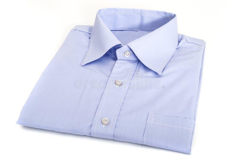 Chemise masculine bleue, pliée d'une manière ordonnée, d'isolement sur le fond blanc image libre de droits