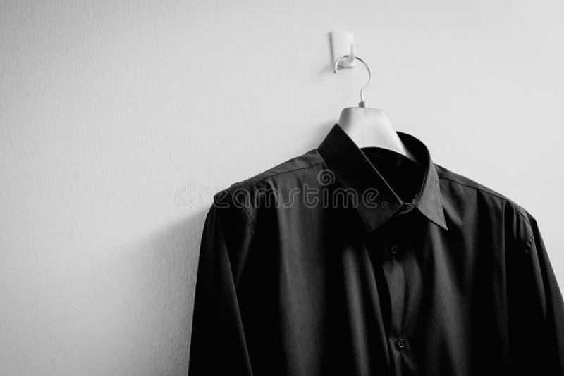 Chemise noire avec le cintre sur le fond blanc images libres de droits