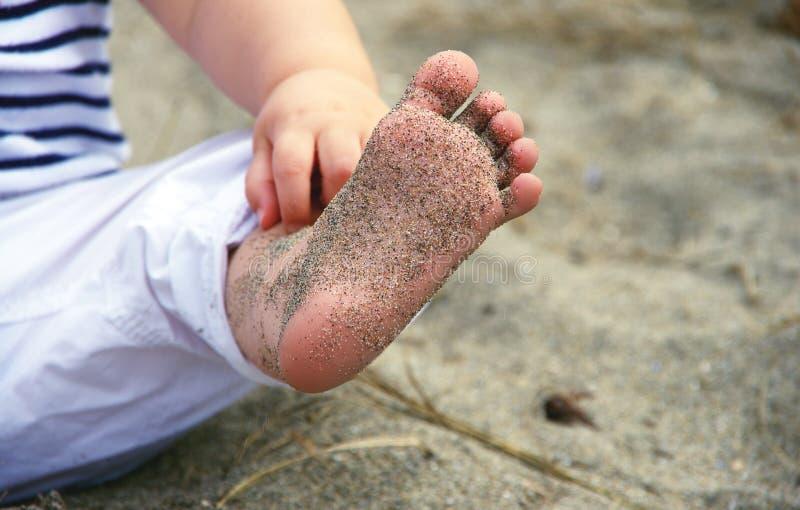 Chemise rayée de port de bébé et pantalon blanc, montrant son pied couvert de sable à une plage à Vancouver, AVANT JÉSUS CHRIST l images stock
