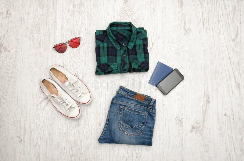 Chemise, verres, espadrilles, jeans, téléphone et passeport à carreaux bleu-vert Fond en bois concept à la mode photographie stock