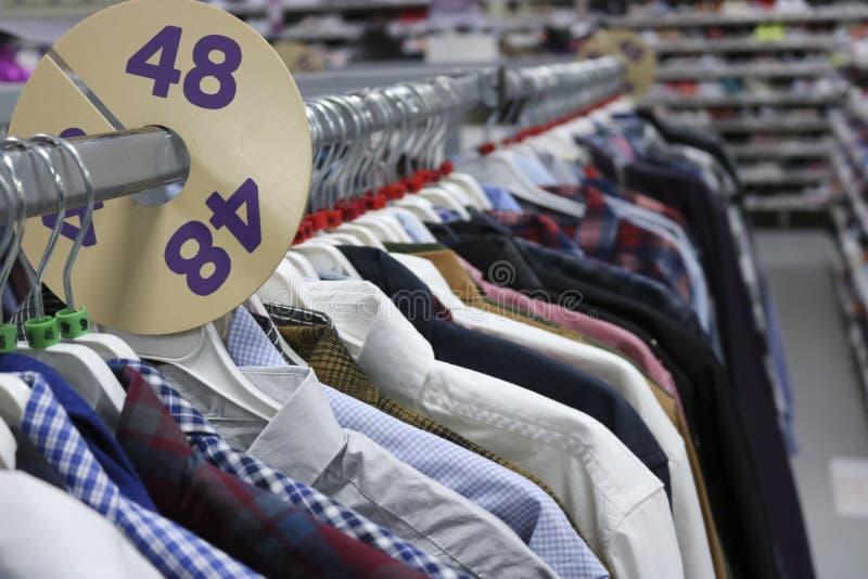 Chemises élégantes sur des cintres dans le magasin brouillé À la veille de Black Friday photographie stock libre de droits