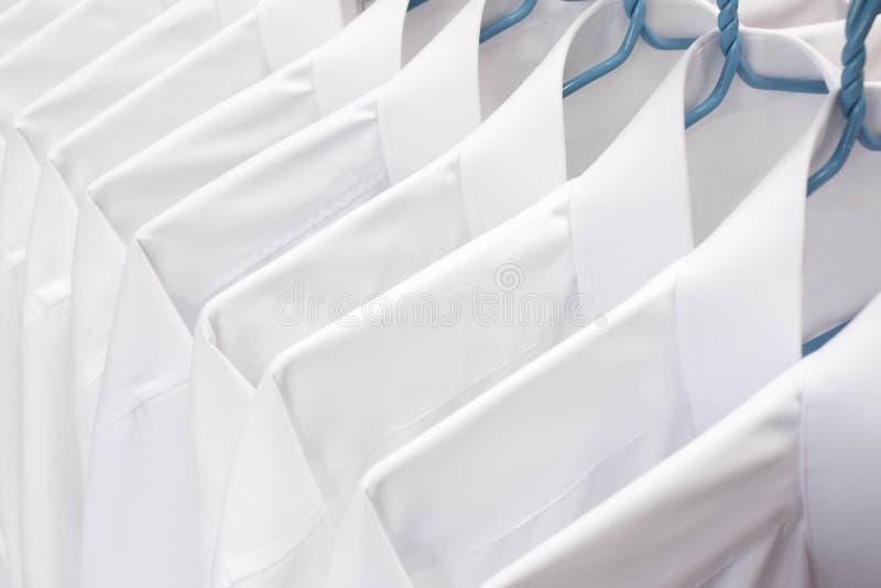 Chemises blanches accrochant sur le support dans une rangée images stock