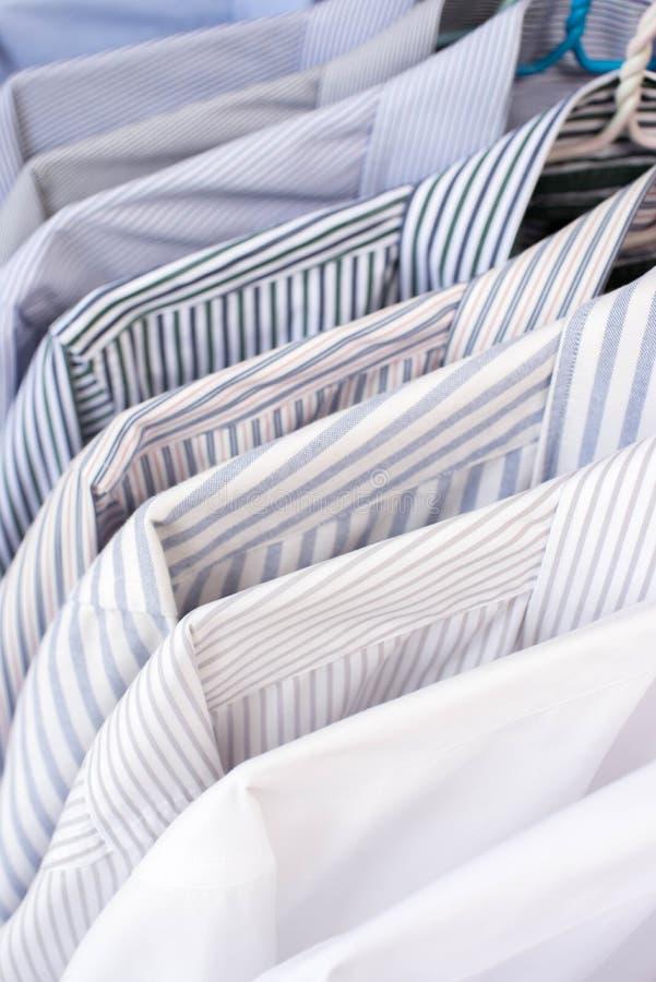 Chemises d'hommes accrochant sur le support dans une rangée, foyer sélectif image libre de droits