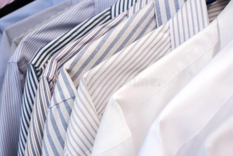 Chemises d'hommes accrochant sur le support dans une rangée, foyer sélectif images libres de droits