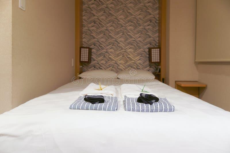 Chemises de nuit et serviette sur le lit blanc dans la chambre d'hôtel japonaise photographie stock