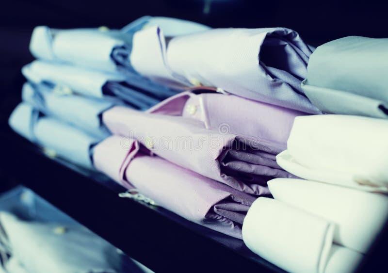 Chemises sur des shelfs dans le magasin d'habillement des hommes images stock