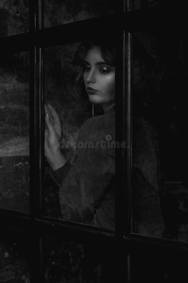 Chemisier de port de modèle à la mode de brune posant derrière la porte en verre Tonalité noire et blanche image stock