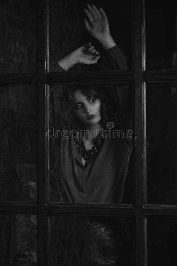 Chemisier et collier de port stupéfiants de modèle de brune posant derrière la porte en verre Tonalité noire et blanche photo libre de droits