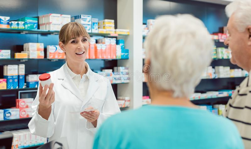 Chemist advising senior couple on a drug in her pharmacy. Chemist advising senior couple on a prescription drug in her pharmacy stock photos