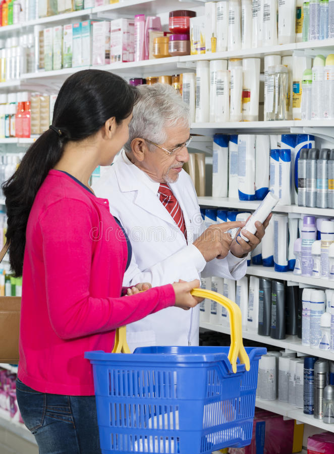 Chemist Assisting Female Customer In Buying Shampoo stock images