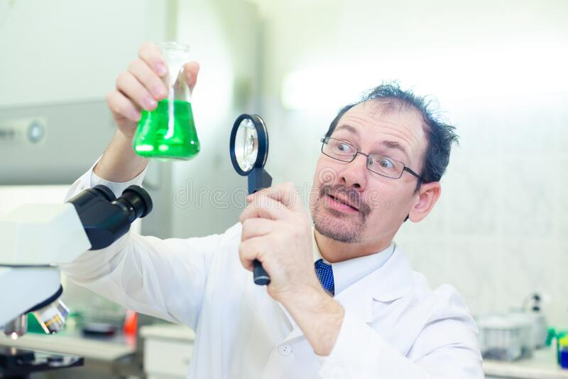 Chemist crazy. A mad scientist conducts experiments in a scientific laboratory. With surprised eyes, he looks through a stock photos