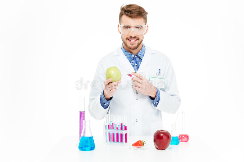 Chemist doing injection of GMOs into apple royalty free stock image