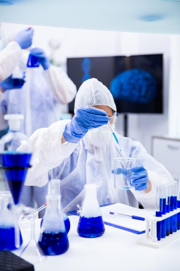 Chemist dripping from the pipette a blue liquid into a container stock photography
