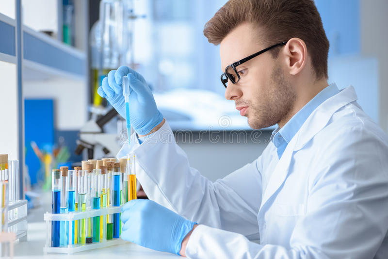 Chemist making experiment in laboratory. Side view of chemist making experiment in laboratory royalty free stock image