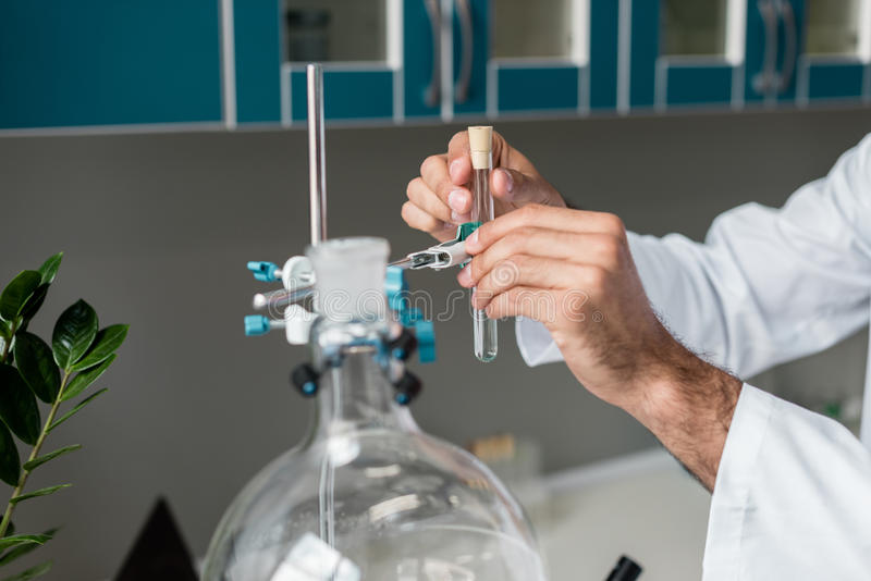 Chemist making experiment with test tubes and flasks in chemical lab. Cropped shot of chemist making experiment with test tubes and flasks in chemical lab stock photography